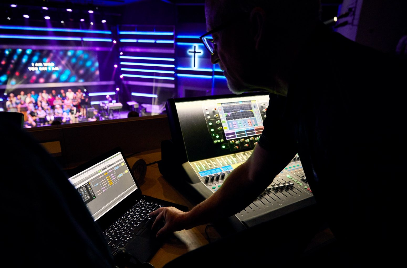 Audio design expert uses sound design system management software during church.